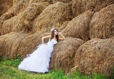 Novia hermosa en pila del heno en su día de boda Foto de archivo