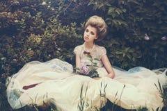 Novia hermosa en un vestido blanco con las flores Fotografía de archivo