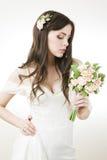 Novia hermosa en un vestido blanco con un ramo Foto de archivo