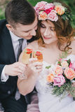 Novia hermosa en un vestido de boda con la guirnalda del ramo y de las rosas que presenta con el traje de la boda del novio que l Foto de archivo libre de regalías