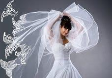 Novia hermosa en una alineada blanca con las mariposas Imagen de archivo libre de regalías
