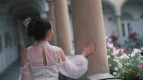 Novia hermosa en vestido elegante, de lujo y el peinado de marfil del updo, presentando cerca de columna metrajes