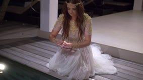 Novia hermosa joven con la vela en la noche cerca de la piscina en el chalet metrajes