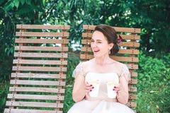 Novia hermosa joven feliz con una taza de café que espera a su novio Café de consumición de la novia hermosa joven en el café del Imágenes de archivo libres de regalías