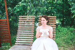 Novia hermosa joven feliz con una taza de café que espera a su novio Café de consumición de la novia hermosa joven en el café del Fotografía de archivo libre de regalías