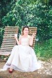 Novia hermosa joven feliz con una taza de café que espera a su novio Café de consumición de la novia hermosa joven en el café del Imagen de archivo libre de regalías