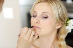 Novia hermosa joven que aplica maquillaje de la boda Imagen de archivo