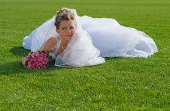 Novia hermosa joven que miente en la hierba verde Imagen de archivo libre de regalías