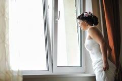 Novia hermosa joven que mira hacia fuera la ventana mientras que sonríe Fotos de archivo