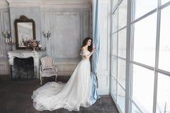 Novia hermosa, mujer morena modelo joven, en vestido de boda elegante con los hombros desnudos, con el ramo de flores adentro Imágenes de archivo libres de regalías