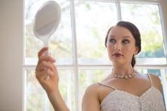 Novia hermosa que mira en el espejo de mano mientras que hace una pausa la ventana en casa Fotografía de archivo libre de regalías