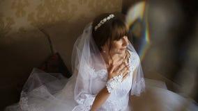 Novia hermosa que presenta cerca de la ventana que sostiene el ramo Mañana del ` s de la novia metrajes