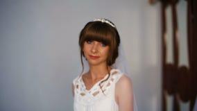 Novia hermosa que presenta cerca de la ventana que sostiene el ramo Mañana del ` s de la novia almacen de video