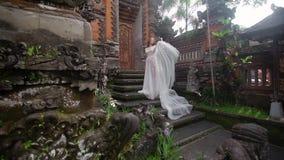 Novia hermosa que presenta cerca del templo budista en Bali El caminar cerca cerca Boda romántica almacen de metraje de vídeo