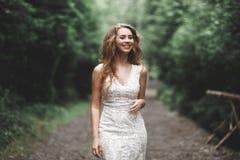 Novia hermosa que presenta en vestido de boda al aire libre Fotos de archivo