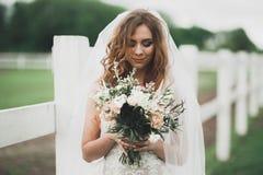 Novia hermosa que presenta en vestido de boda al aire libre Foto de archivo