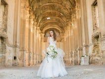 Novia hermosa romántica en la presentación de lujo del vestido de la arquitectura hermosa Imagen de archivo libre de regalías