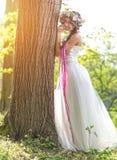 Novia hermosa, tiara de la flor en su cabeza, confiando en el árbol Fotos de archivo
