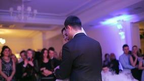 Novia hermosa y novio hermoso que bailan primero danza en el banquete de boda almacen de video
