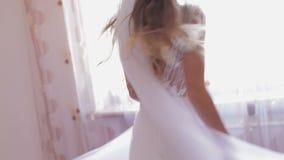 Novia hermosa y preciosa en el baile del vestido de boda cerca de la ventana Mañana de la boda Mujer bonita y bien arreglada Cáma metrajes