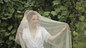 Novia hermosa y preciosa en vestido de la noche y velo en el jard?n Ma?ana de la boda almacen de metraje de vídeo