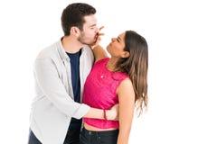 Novia infeliz que bloquea el beso del novio sobre fondo llano imagenes de archivo