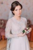 Novia inocente linda en casa en el vestido de boda blanco, concepto de las preparaciones Retrato de la muchacha blanda en vestido Imagenes de archivo