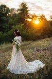 Novia joven afuera en un prado del verano en la puesta del sol Imagenes de archivo