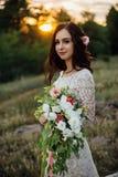 Novia joven afuera en un prado del verano en la puesta del sol Imágenes de archivo libres de regalías