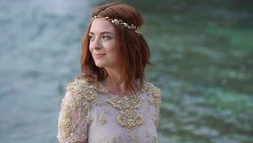 Novia joven en la playa cerca del mar en la igualación o sunsetposing Océano cercano romántico metrajes