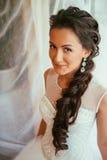 Novia joven hermosa con maquillaje de la boda y peinado en el dormitorio, preparación final de la mujer del recién casado para ca foto de archivo