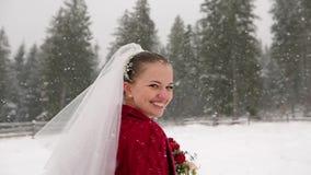 Novia joven que corre al bosque que pide seguirla y que se divierte en el pueblo de la estación de esquí bajo nevadas pesadas Inv almacen de video