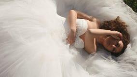 Novia joven sensual en el vestido de boda blanco que miente en césped de la hierba verde y que mira atractivo la cámara almacen de metraje de vídeo