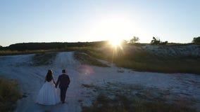 Novia joven y novio hermosos y felices de los pares que caminan en la puesta del sol en el día de su boda Paseo abajo de la colin almacen de metraje de vídeo