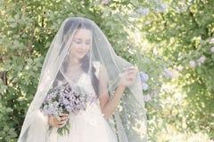 Novia linda hermosa blanda de la muchacha en un vestido blanco del aire con un ramo de lilas en sus manos que caminan a través de imágenes de archivo libres de regalías