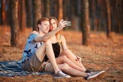 Novia linda y novio que toman un selfie en el fondo del bosque del otoño Concepto adolescente de la datación Fotos de archivo libres de regalías