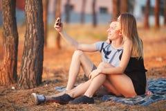Novia linda y novio que toman un selfie en el fondo del bosque del otoño Concepto adolescente de la datación Imágenes de archivo libres de regalías