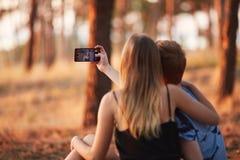 Novia linda y novio que toman un selfie en el fondo del bosque del otoño Concepto adolescente de la datación Imagen de archivo