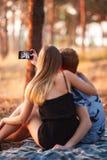 Novia linda y novio que toman un selfie en el fondo del bosque del otoño Concepto adolescente de la datación Foto de archivo libre de regalías