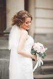 Novia maravillosa con un vestido blanco lujoso que presenta en la ciudad vieja foto de archivo libre de regalías