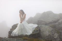 Novia misteriosa que se sienta en el top de la montaña rocosa Foto de archivo libre de regalías