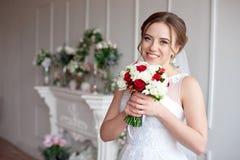 Novia morena con el peinado clásico de la boda, sonriendo tomando el ramo de la boda en sus manos Fotos de archivo libres de regalías