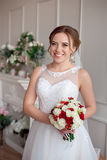Novia morena con el peinado clásico de la boda, sonriendo tomando el ramo de la boda en sus manos Fotografía de archivo