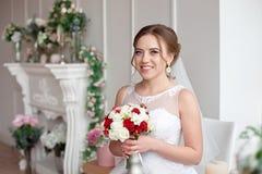Novia morena con el peinado clásico de la boda, sonriendo tomando el ramo de la boda en sus manos Imagen de archivo
