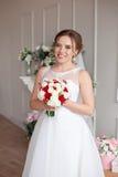 Novia morena con el peinado clásico de la boda, sonriendo tomando el ramo de la boda en sus manos Imagenes de archivo