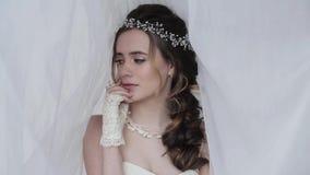 Novia morena en el vestido de boda blanco de la moda con maquillaje almacen de video