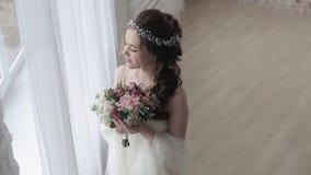 Novia morena en el vestido de boda blanco de la moda con maquillaje metrajes