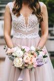Novia morena en un vestido de boda rosado hermoso con bordado en un corsé que sostiene un ramo de peonías fotos de archivo libres de regalías