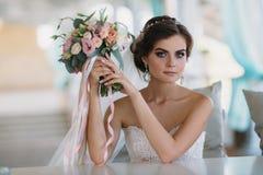 Novia morena hermosa joven en el vestido blanco con maquillaje, el peinado y el ramo hermosos de flores concepto de la boda Foto de archivo libre de regalías