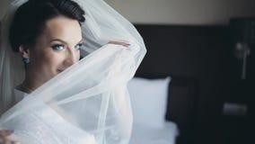 Novia morena hermosa que presenta al fotógrafo Mujer que sonríe, pieles detrás de un velo Hembra con maquillaje hermoso metrajes